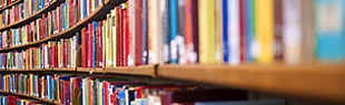 Das Bild zeigt ein Regal einer Bibliothek gefüllt mit Büchern. Vorn, auf der rechten Seite etwas unscharf, nach hinten auf der linken Seite deutlicher werdend mit fünf Regalböden.