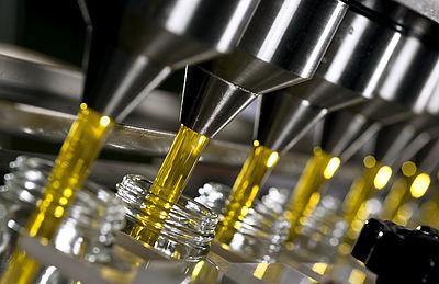 Das Bild zeigt eine Abfüllanlage, die gelbe Flüssigkeit in Einmachgläser abfüllt.