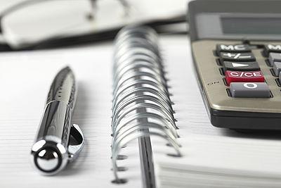 Auf dem Bild liegen ein Taschenrechner und ein Kugelschreiber auf einem Ringbuch.
