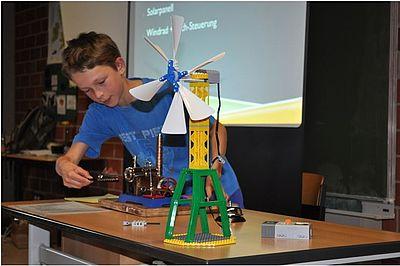 Das Bild zeigt einen Schüler, der ein teschnisches Projekt vorstellt. Im Hintergund ist die Projektion eines Beamers auf einer Leinwand vor einer Tafel zu sehen.