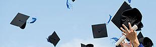 Das Bild zeigt Absolventenhüte, die in die Luft geworfen werden, und ein Zeugnis gerollt in einer Hand gehalten wird.