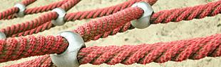 Das Bild zeigt das Netz eines Kletternetzes auf sandigem Boden.
