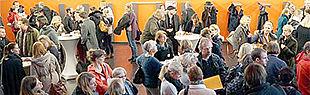 Das Foto zeigt viele Menschen im Foyer des Audimax verteilt an einigen Stehtischen.