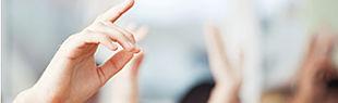 Das Bild zeigt eine aufzeigende Hand im Fokus mit mehreren verblassenden aufzeigenden Händen im Hintegrund.