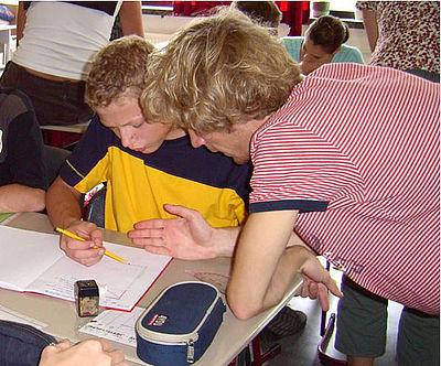 Das Bild zeigt eine männliche Junge Lehrkraft, die einen Schüler an einem Tisch berät. Im Hintergrund sind weitere SchülerInnen zu sehen.