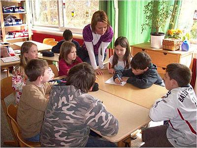Das Bild zeigt eine weibliche Lehrkraft, die einer Gruppe von SchülerInnen an einem Gruppentisch in einem Klassenraum etwas erklärt. im Hintergrund ist ein weiterer Schüler zu sehen.