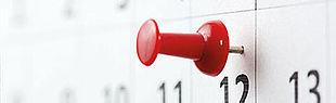 Das Bild zeigt einen Wandkalender mit einer roten Stecknadel auf einem Tag.