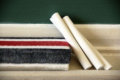 Das Bild zeigt vier Stücke Kreide an einen Schwamm gelehnt auf einer Ablage vor einer Tafel.